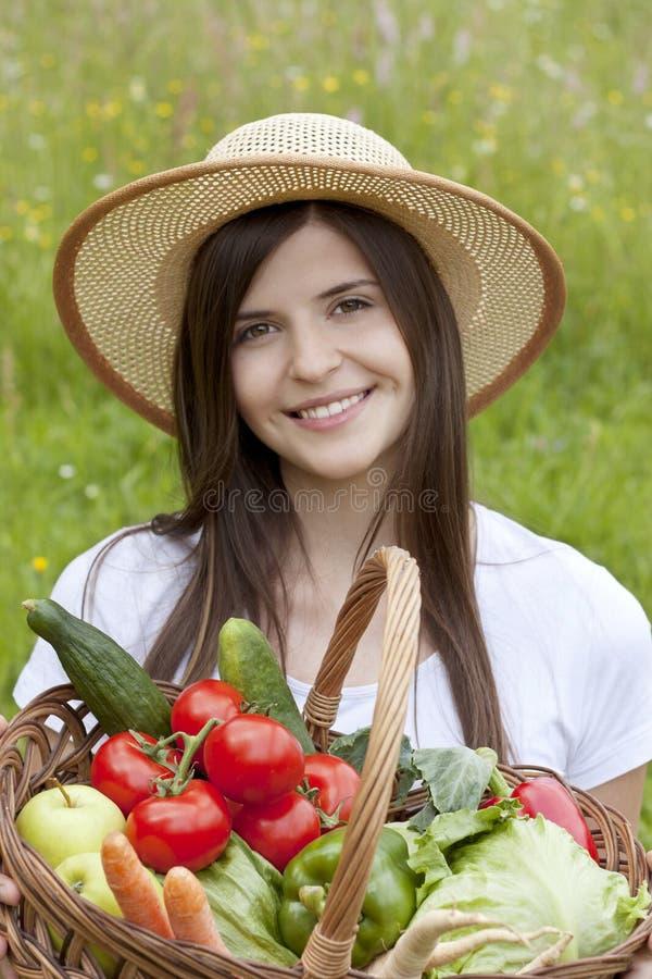Ragazza graziosa che tiene un cestino delle verdure fotografie stock