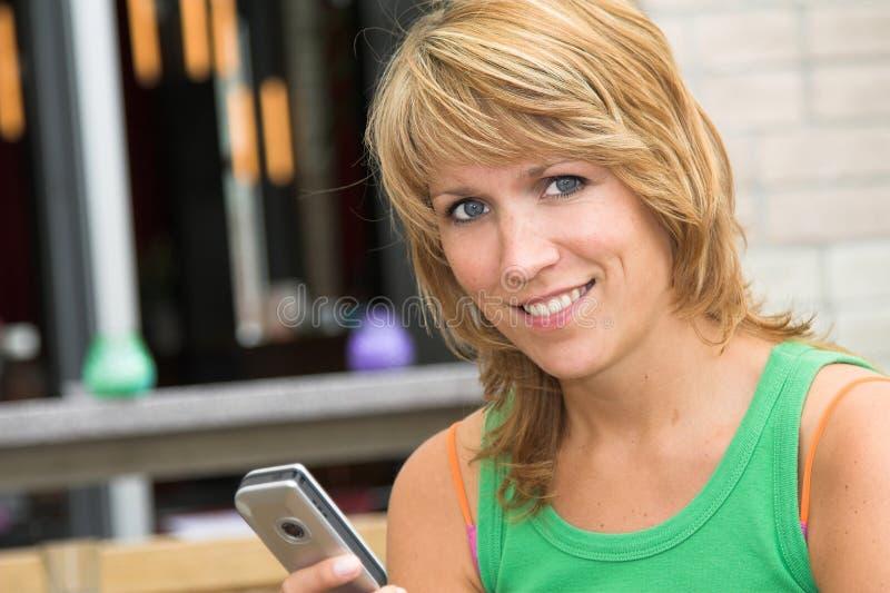 Ragazza graziosa che trasmette i messaggi di testo fotografia stock