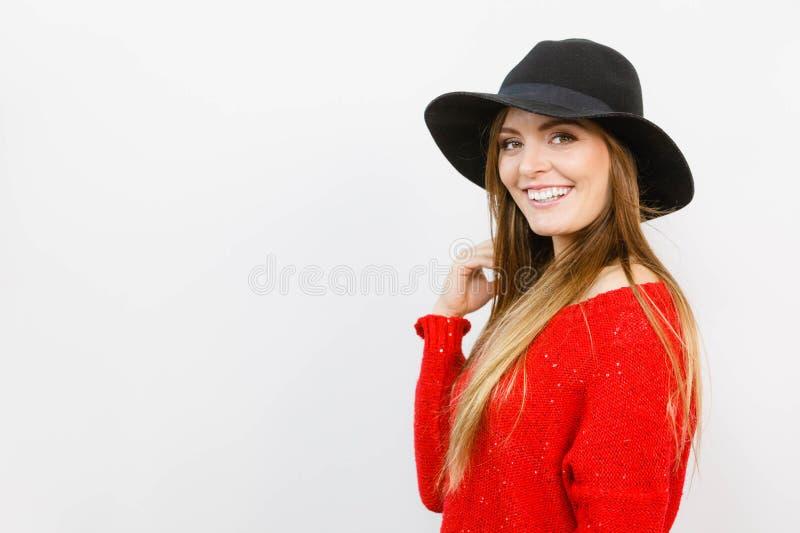 Ragazza graziosa con capelli marroni e black hat sorridenti immagini stock libere da diritti