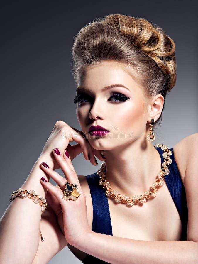 Ragazza graziosa con i bei gioielli dell'oro e dell'acconciatura, m. luminosa immagini stock