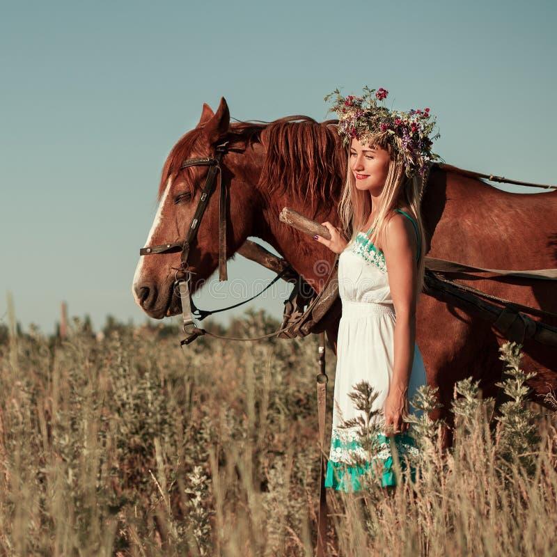Ragazza graziosa con i wildflowers sul trasporto del cavallo nel giorno di estate immagini stock libere da diritti