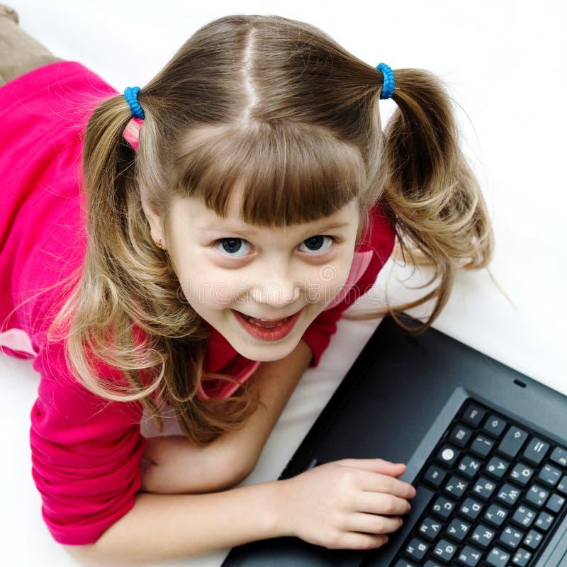 Ragazza graziosa con il computer portatile fotografie stock libere da diritti