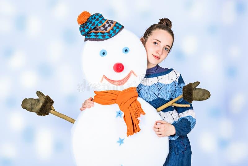 Ragazza graziosa con il suo pupazzo di neve dell'amico immagine stock