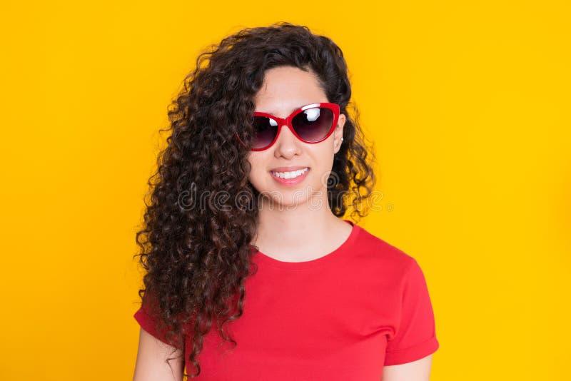 Ragazza graziosa con l'acconciatura riccia su fondo giallo Bello ritratto della donna in maglietta rossa che sorride e che esamin immagine stock