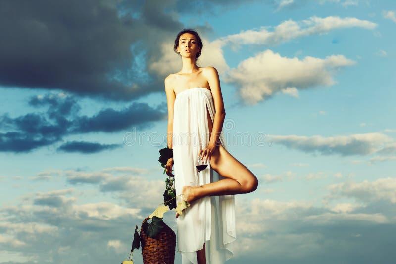 Ragazza graziosa con la bottiglia di vino sopra il cielo immagini stock libere da diritti