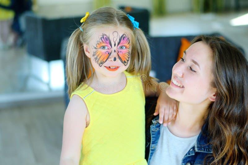 Ragazza graziosa con la pittura del fronte di una farfalla con la babysitter fotografia stock