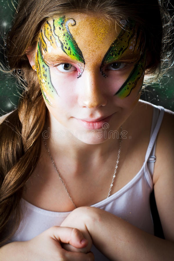 Ragazza graziosa con la pittura del fronte sul fondo nero fotografia stock