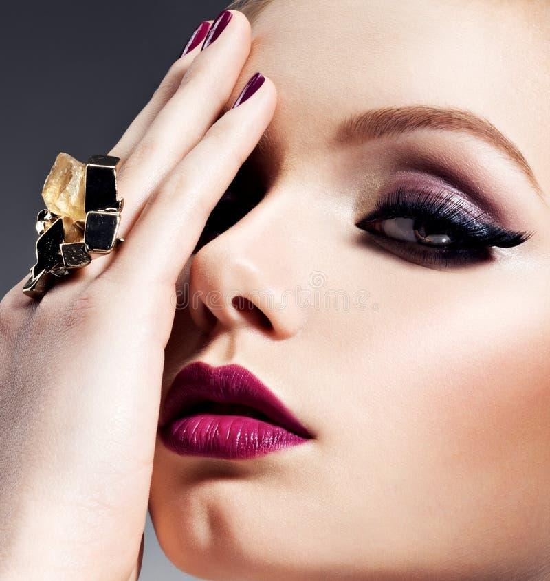 Ragazza graziosa con trucco luminoso del bello fronte ed i gioielli dell'oro fotografia stock