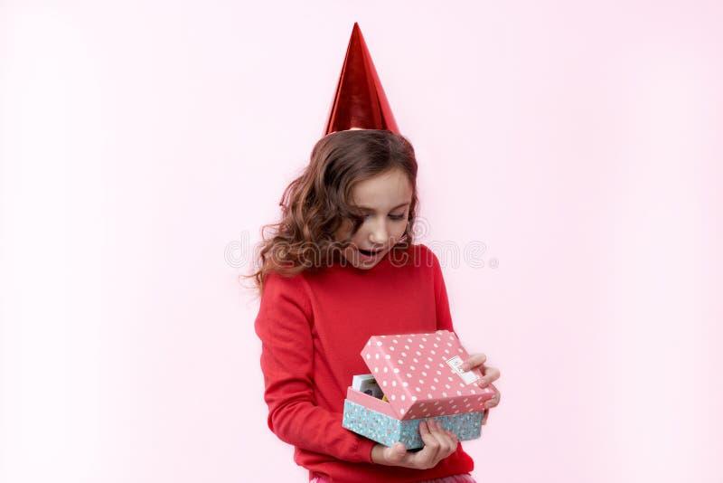 Ragazza graziosa con un cappuccio di compleanno sulla sua testa con stupita fotografia stock libera da diritti