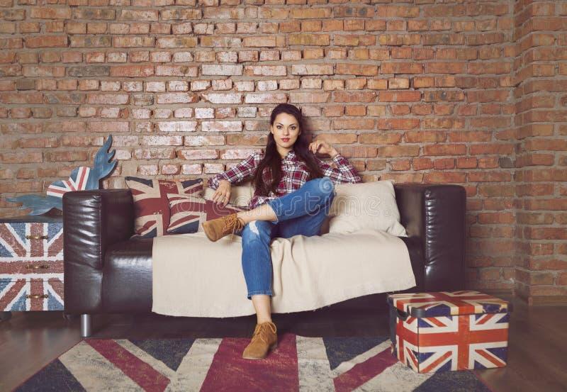 Ragazza graziosa dei pantaloni a vita bassa che si siede sullo strato a casa fotografia stock