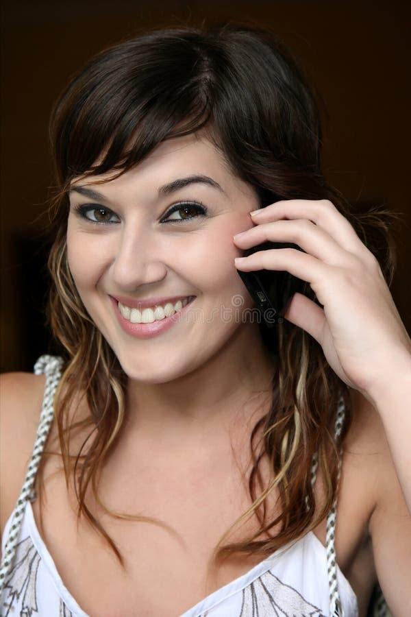 Ragazza graziosa del Brunette con il telefono delle cellule fotografia stock