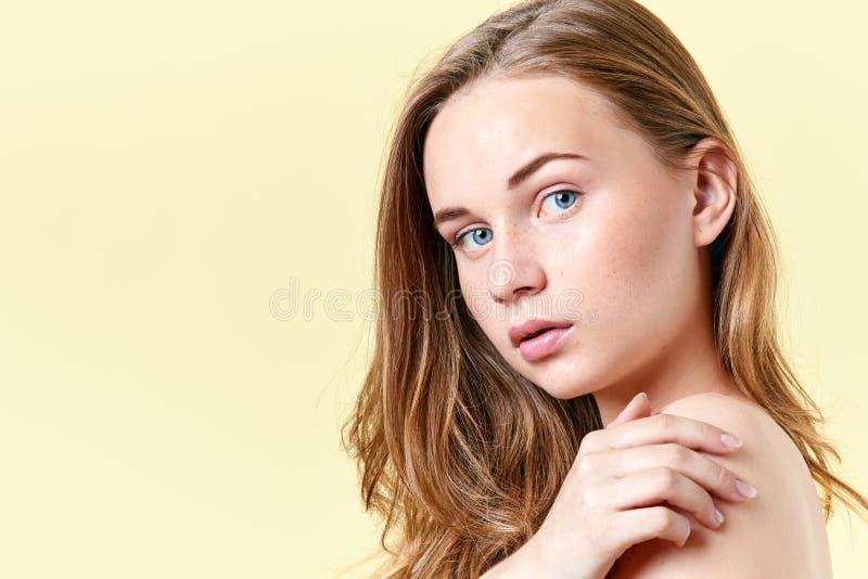 Ragazza graziosa dell'adolescente della testarossa con gli occhi azzurri e le lentiggini, con le spalle nude, esaminanti macchina fotografia stock