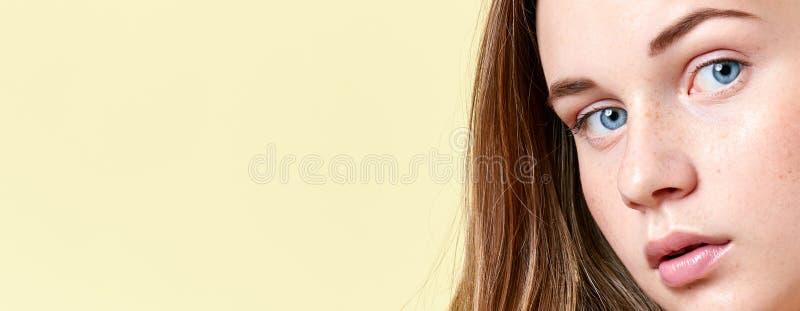 Ragazza graziosa dell'adolescente della testarossa con gli occhi azzurri e le lentiggini, con le spalle nude, esaminanti macchina fotografie stock
