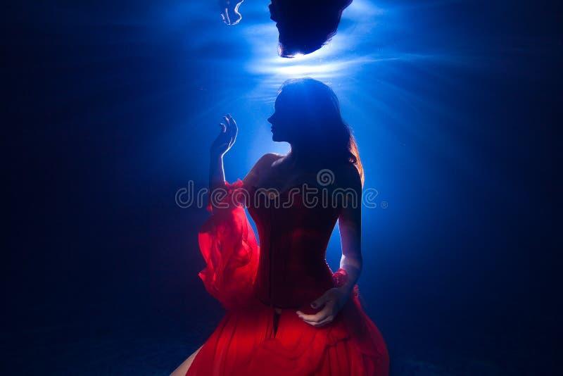 Ragazza graziosa della foto subacquea con l'uso lungo scuro dei capelli fotografia stock