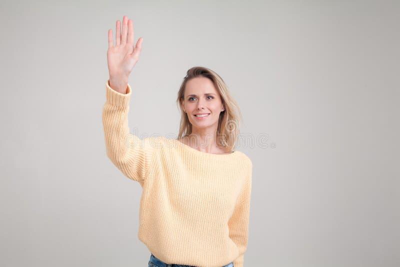 Ragazza graziosa dello studente che dice ciao, sorridendo allegro ed amichevole, ondeggiando la sua mano pose contro fondo grigio fotografia stock libera da diritti