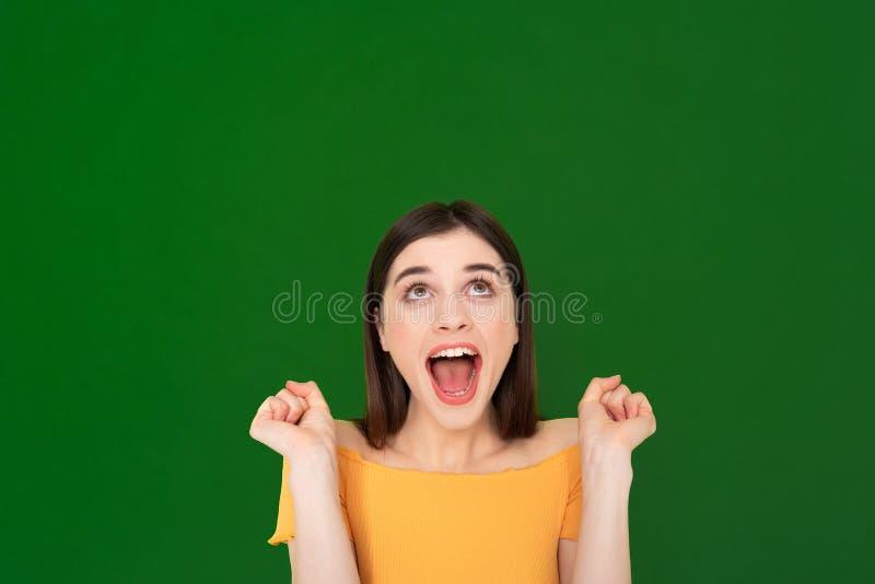 Ragazza graziosa emozionante felice isolata su verde immagini stock