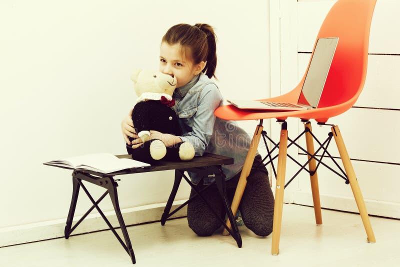 Ragazza graziosa felice che sorride al giocattolo dell'orsacchiotto fotografia stock