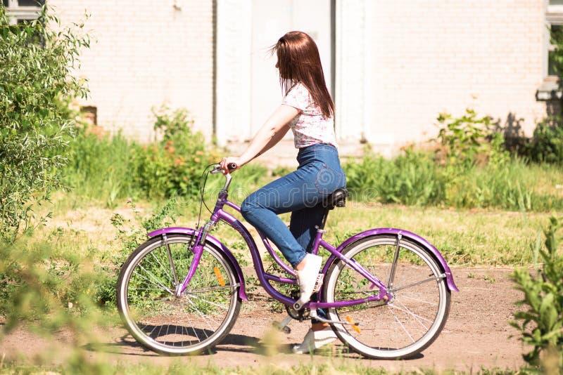 Ragazza graziosa felice che va in bicicletta sul parco di estate Felice rilassi il tempo in città Bella donna, giorno soleggiato fotografia stock