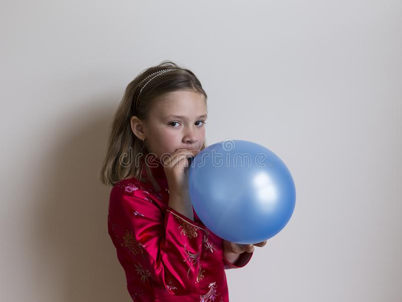 Ragazza graziosa nell'esplosione rossa un pallone blu immagini stock libere da diritti