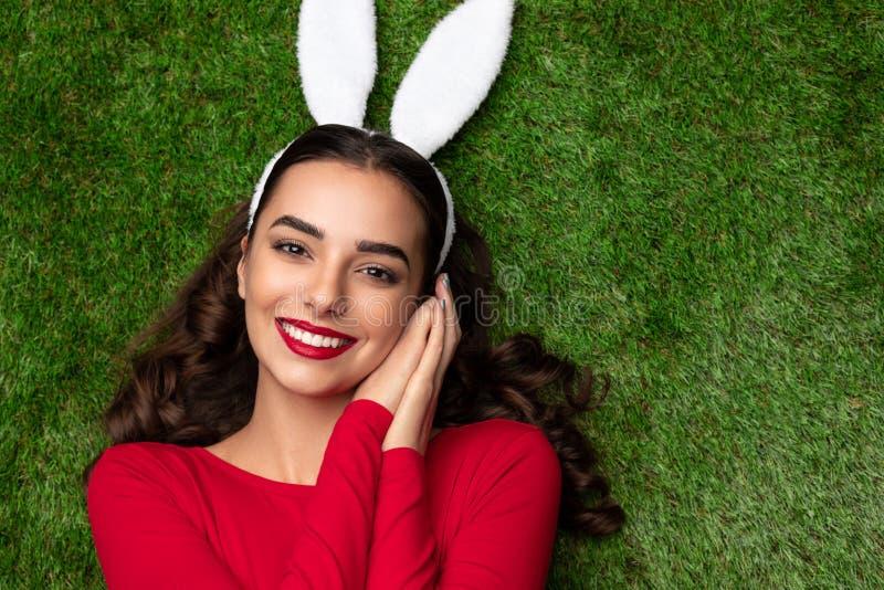 Ragazza graziosa in orecchie del coniglietto che si trovano sul prato immagine stock libera da diritti