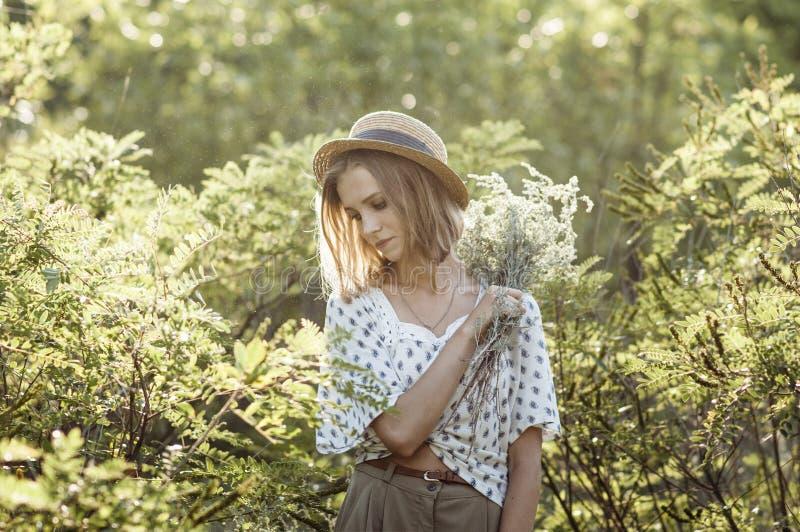 Ragazza graziosa pensierosa in un cappello di paglia fotografia stock libera da diritti