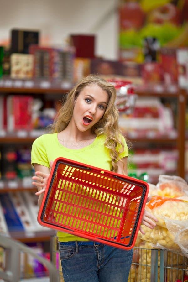 Ragazza graziosa sorpresa che mostra canestro rosso vuoto alla drogheria fotografie stock libere da diritti