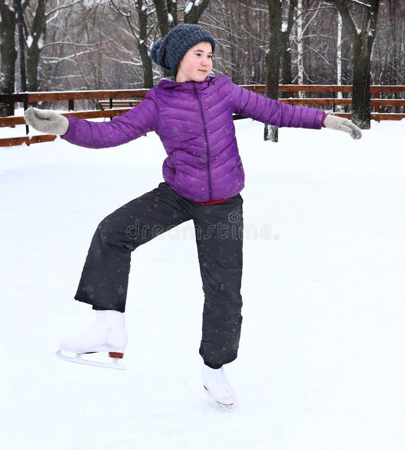 Ragazza graziosa teenager che pattina sulla pista di pattinaggio sul ghiaccio immagini stock