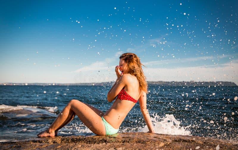 Ragazza graziosa in un bikini accanto all'oceano che ride come è spruzzata da un'onda che si schianta sulle rocce fotografia stock libera da diritti