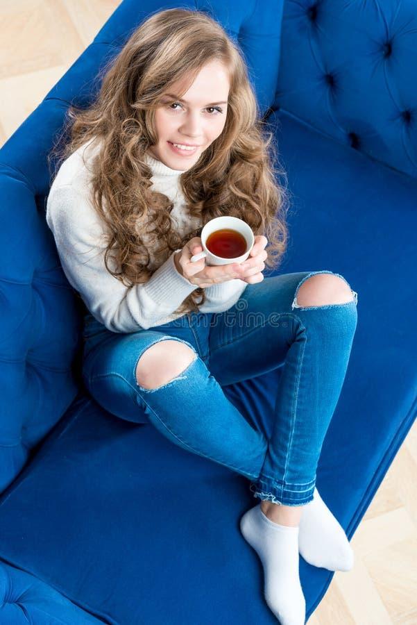 Ragazza graziosa in un maglione caldo con una tazza di tè sul sofà nella t immagini stock libere da diritti