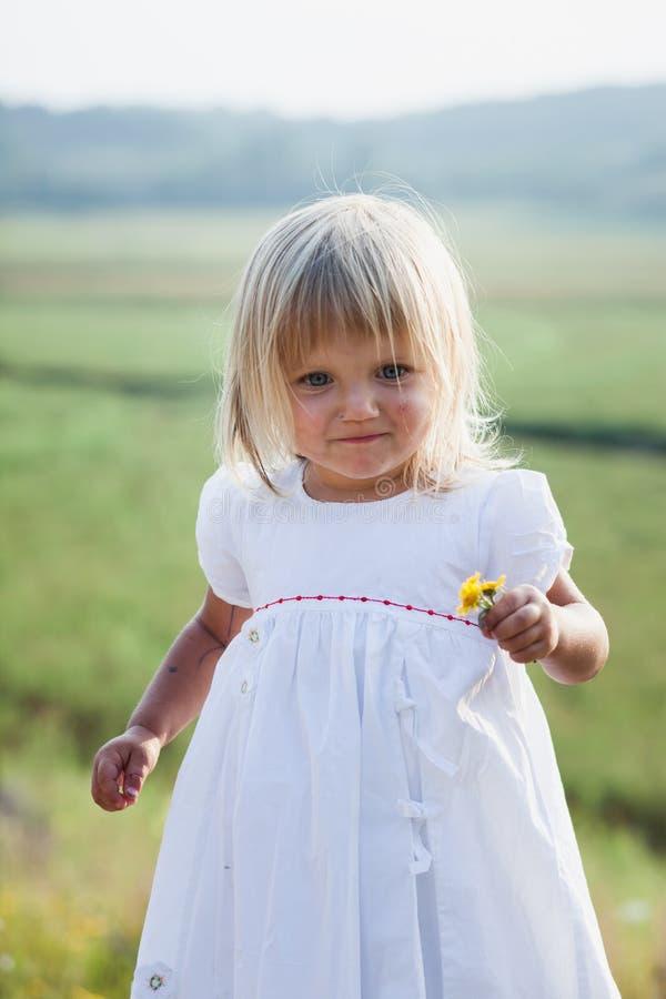 Ragazza graziosa in vestito bianco accanto allo stagno fotografia stock libera da diritti