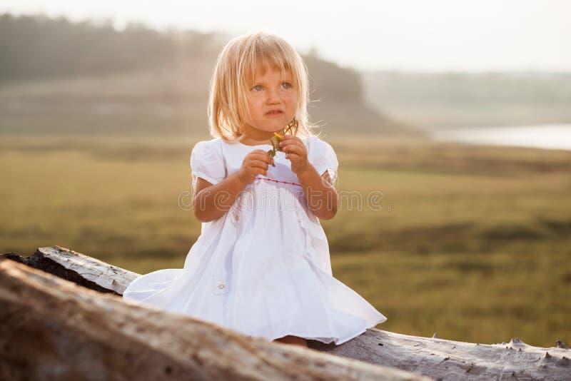 Ragazza graziosa in vestito bianco accanto allo stagno fotografie stock