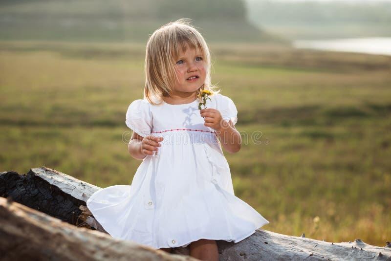 Ragazza graziosa in vestito bianco accanto allo stagno fotografia stock