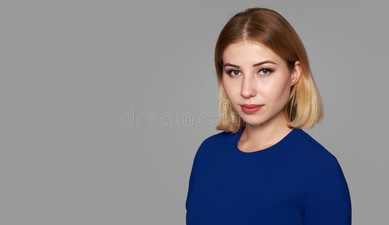 Ragazza graziosa in vestito blu su grigio fotografie stock