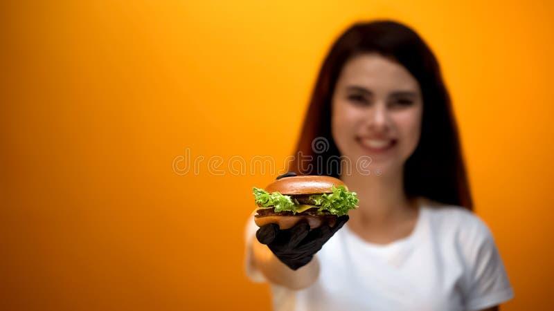 Ragazza in hamburger di rappresentazione del guanto alla macchina fotografica, alimenti a rapida preparazione saporiti, servizio  fotografia stock libera da diritti