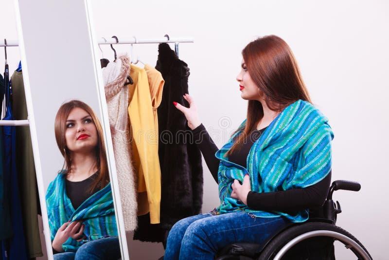 Ragazza handicappata sulla sedia a rotelle che sceglie i vestiti immagine stock