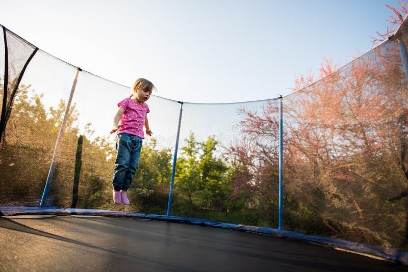 Ragazza impaurita di salto sul letto del trampolino immagine stock