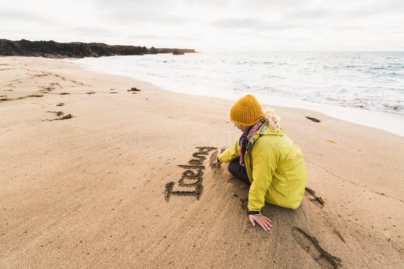 Ragazza in impermeabile giallo che scrive la parola Islanda sulla sabbia della spiaggia al tramonto, penisola di Skardsvik di Sna immagine stock