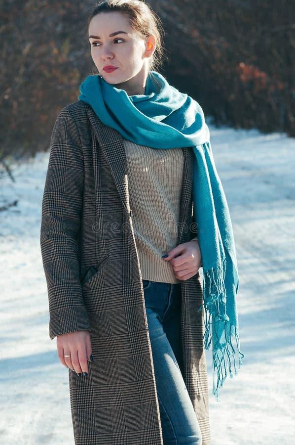 Ragazza incantante, sciarpa blu e jeans, cappotto marrone, modo fotografie stock libere da diritti