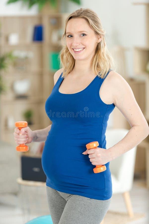 Ragazza incinta che tiene dummbell immagine stock