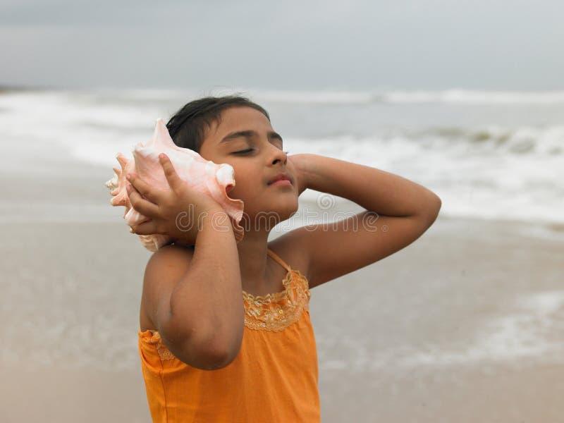 Ragazza indiana che ascolta una conca fotografia stock