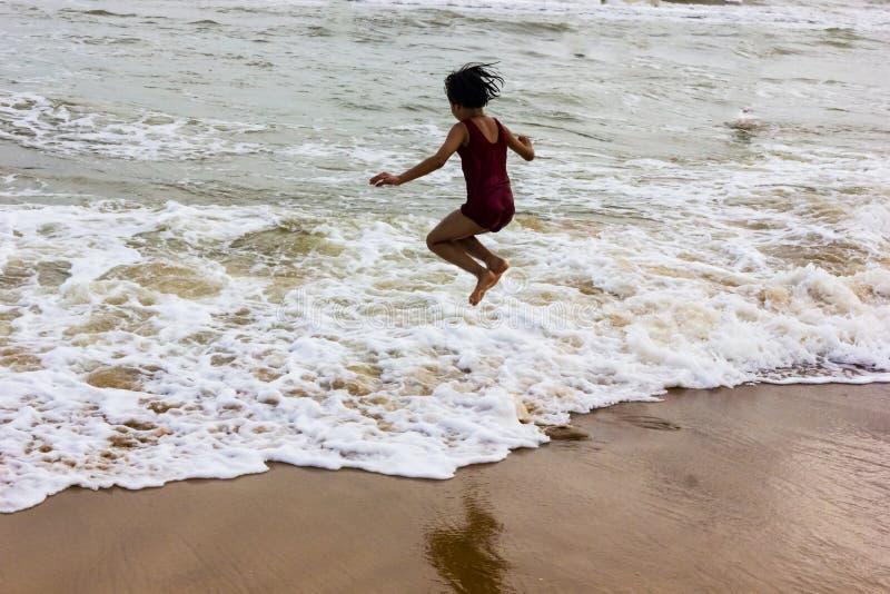 Ragazza indiana del bambino che salta contro l'onda d'avvicinamento sulla spiaggia sabbiosa di puri in spiaggia che esprime gioia fotografia stock