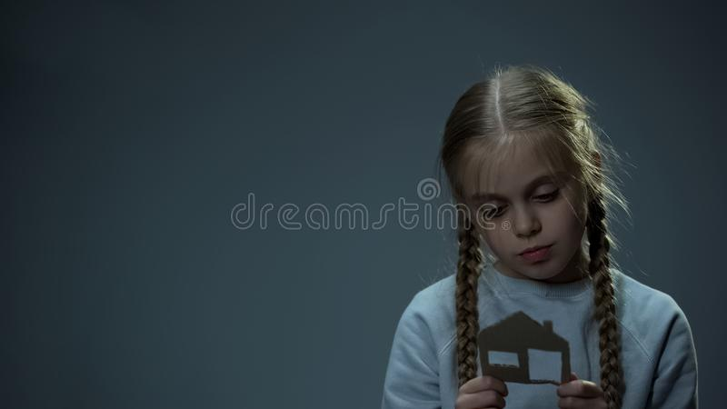 Ragazza infelice che esamina la casa della carta, bambino orfano che sogna della casa, tristezza immagine stock
