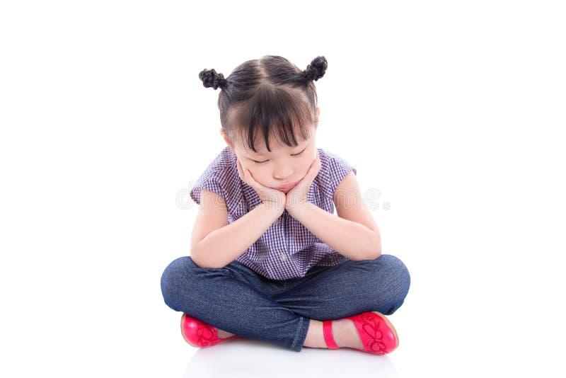 Ragazza infelice che si siede sul pavimento isolato sopra bianco immagine stock