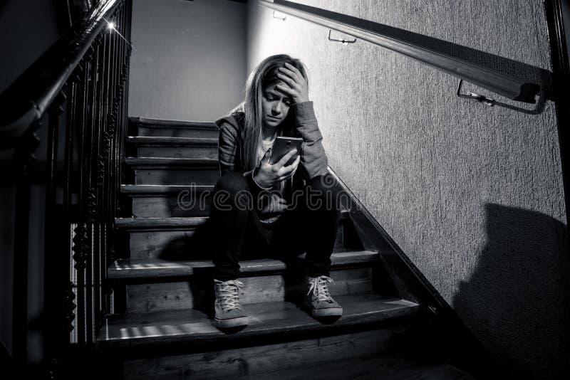 Ragazza infelice depressa triste dell'adolescente che soffre dal cyberbullismo dallo Smart Phone mobile che si siede da solo immagine stock libera da diritti