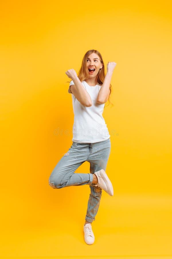Ragazza integrale e entusiasta, celebrante successo su un fondo giallo immagine stock