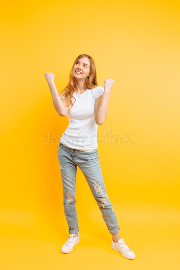 Ragazza integrale e entusiasta, celebrante successo su un fondo giallo fotografia stock libera da diritti