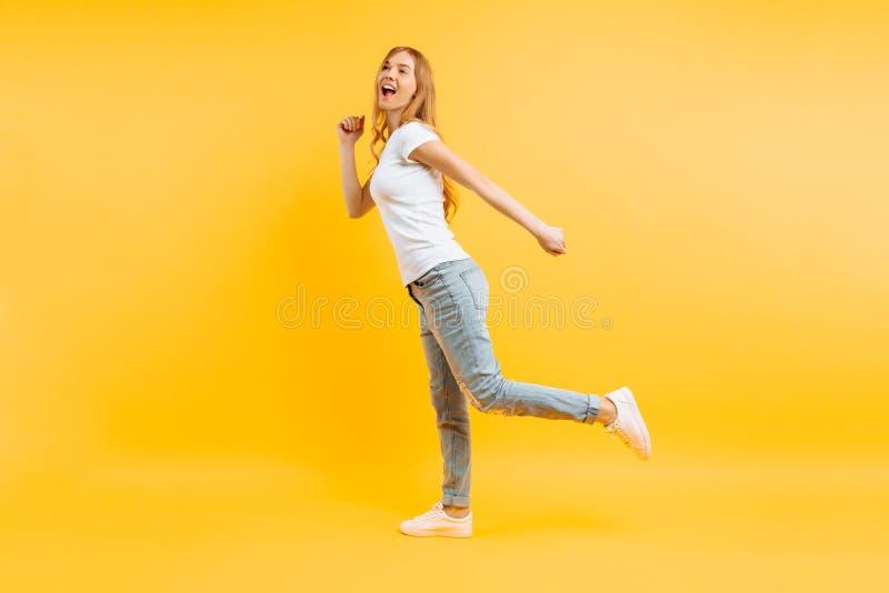 Ragazza integrale e positiva che cammina su un fondo giallo immagine stock