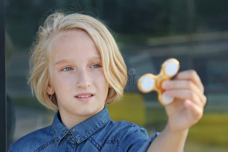 Ragazza invecchiata scuola bionda sveglia allegra che gioca con un filatore di irrequietezza dell'oro Un giocattolo d'avanguardia fotografia stock libera da diritti