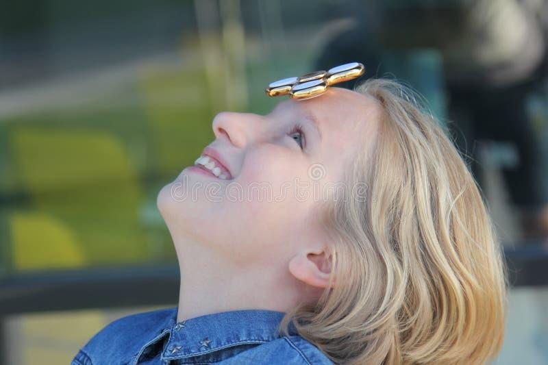 Ragazza invecchiata scuola sveglia allegra che gioca con un filatore di irrequietezza dell'oro Un giocattolo d'avanguardia popola immagine stock