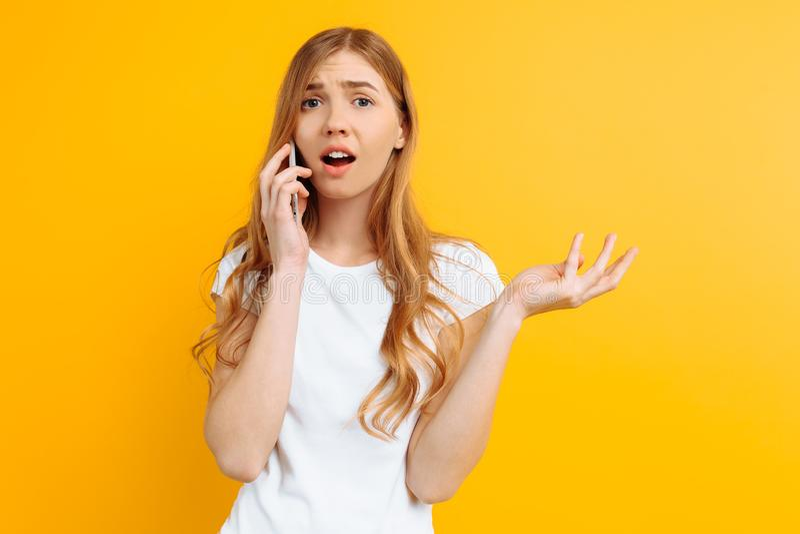 Ragazza irritata ed incerta che parla sul telefono, su un fondo giallo immagini stock libere da diritti
